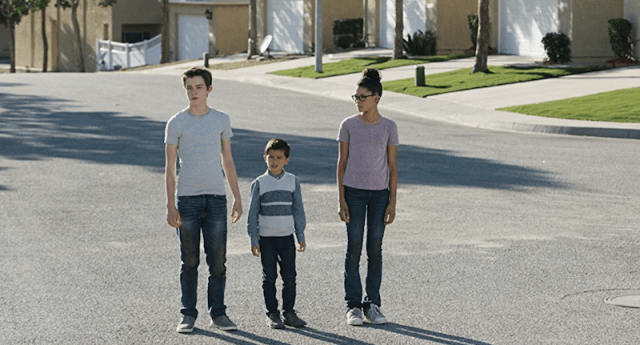 Meg, Calvin and Charles standing in a neighborhood.