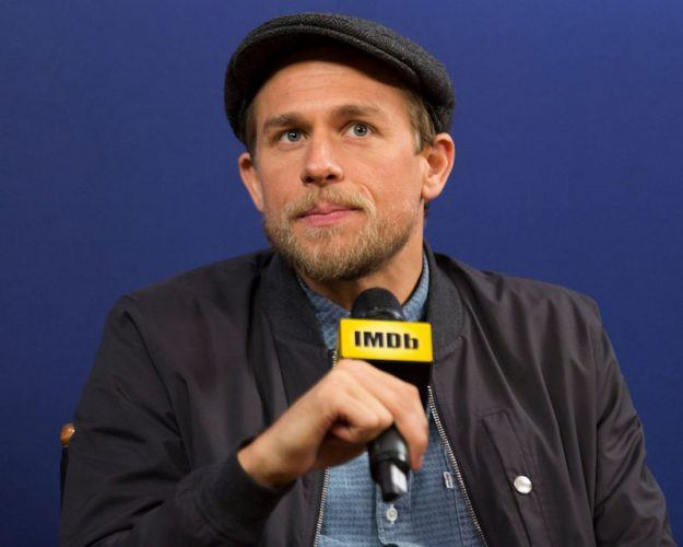 Charlie Hunnam holding up a microphone during an interview.