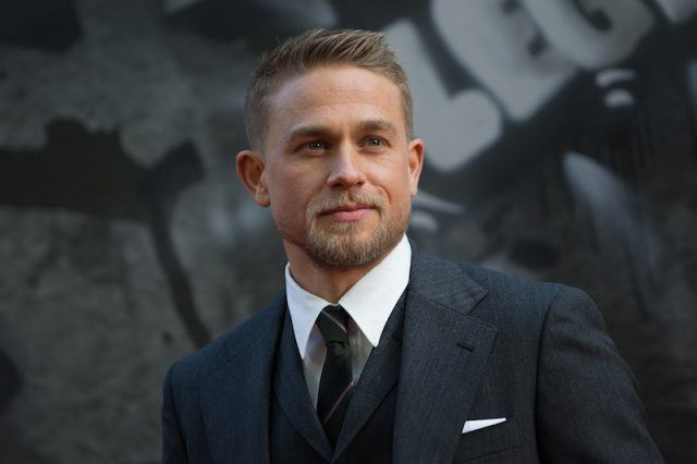 Charlie Hunnam standing in a dark suit, tie and vest.