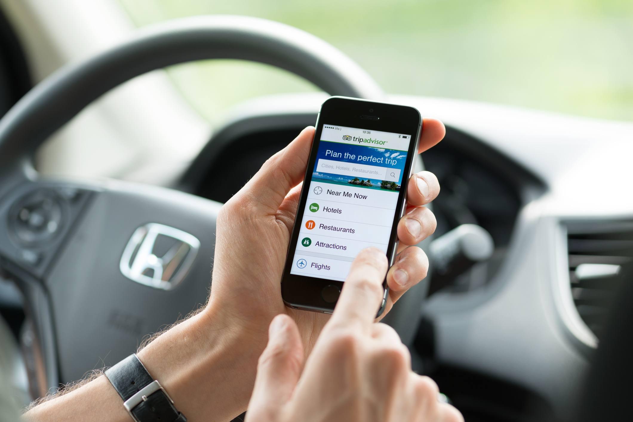 Man in car with TripAdvisor app open.