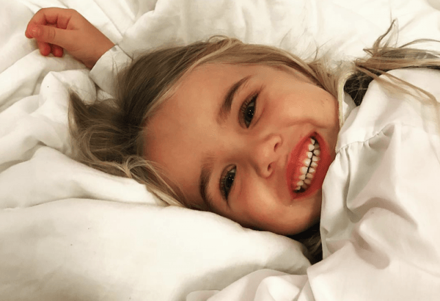 Chloe smiling while laying on sheets.