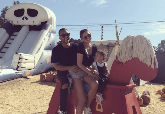 Chrissy Teigen, John Legend and Luna on a wooden horse at a playground.