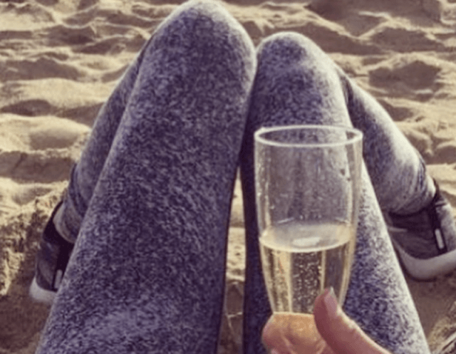 Christina drinks champagne on the beach.