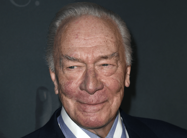 Christopher Plummer wearing a striped shirt and a suit.