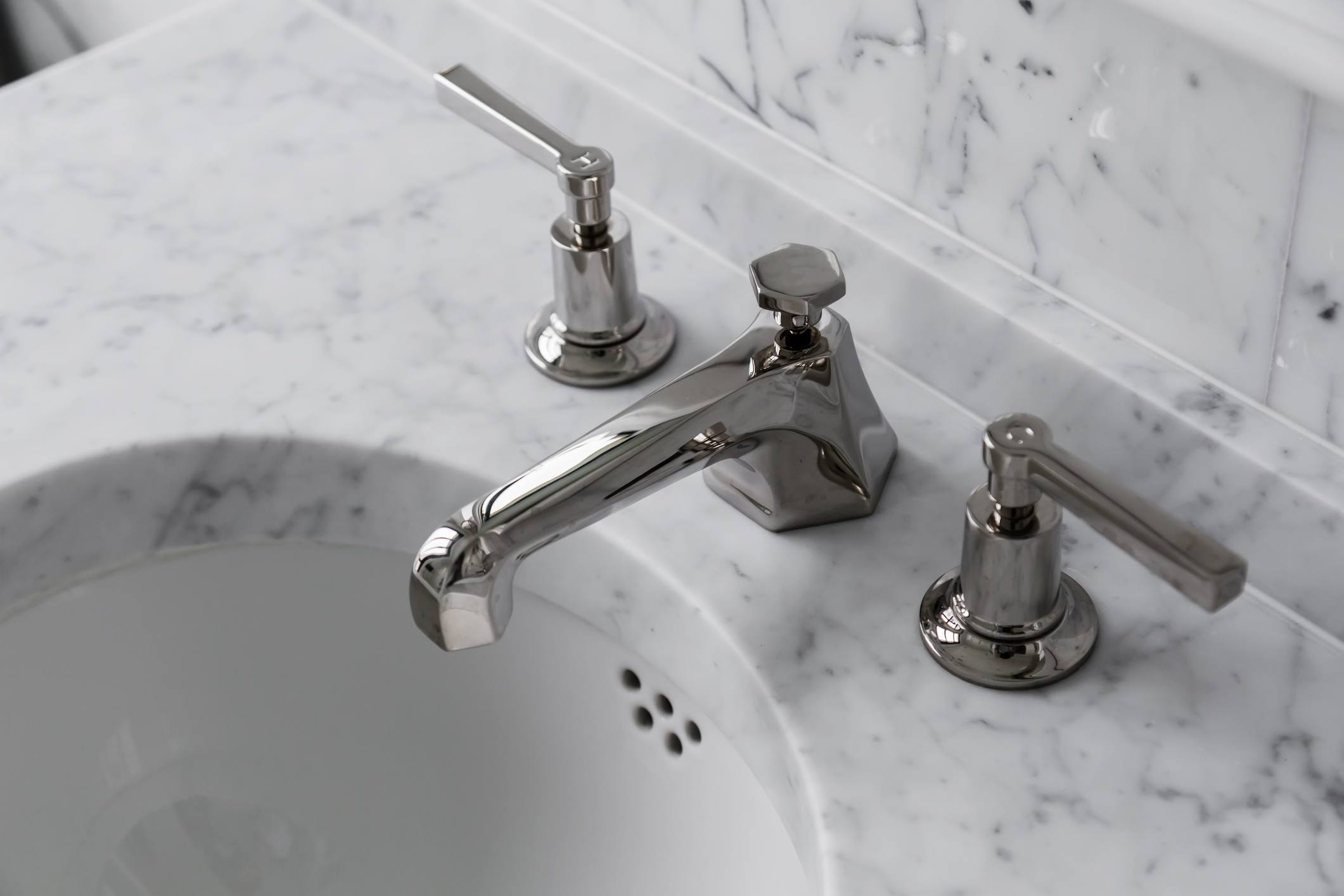 closeup faucet and lavatory white marble restroom interior concept