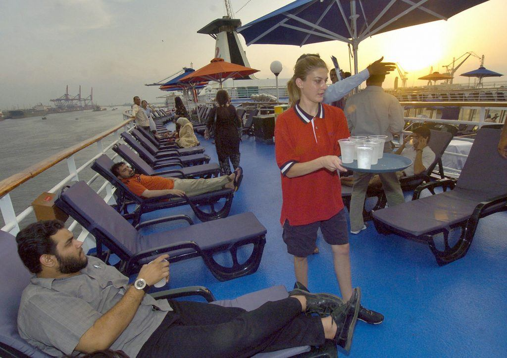 A foreign crew member serves drinks on cruise ship