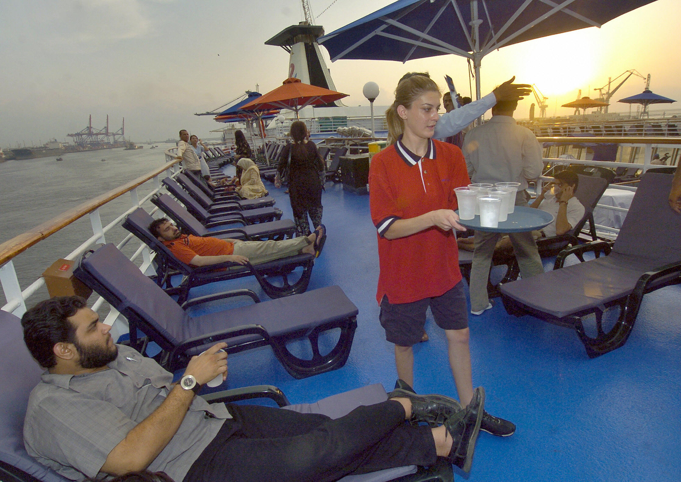 A foreign crew member serves drink on cruise ship