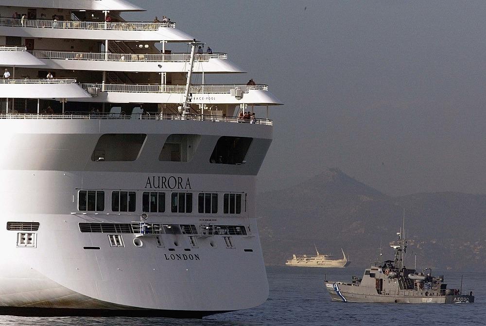 A Greek coast guard boat patrols around a cruise