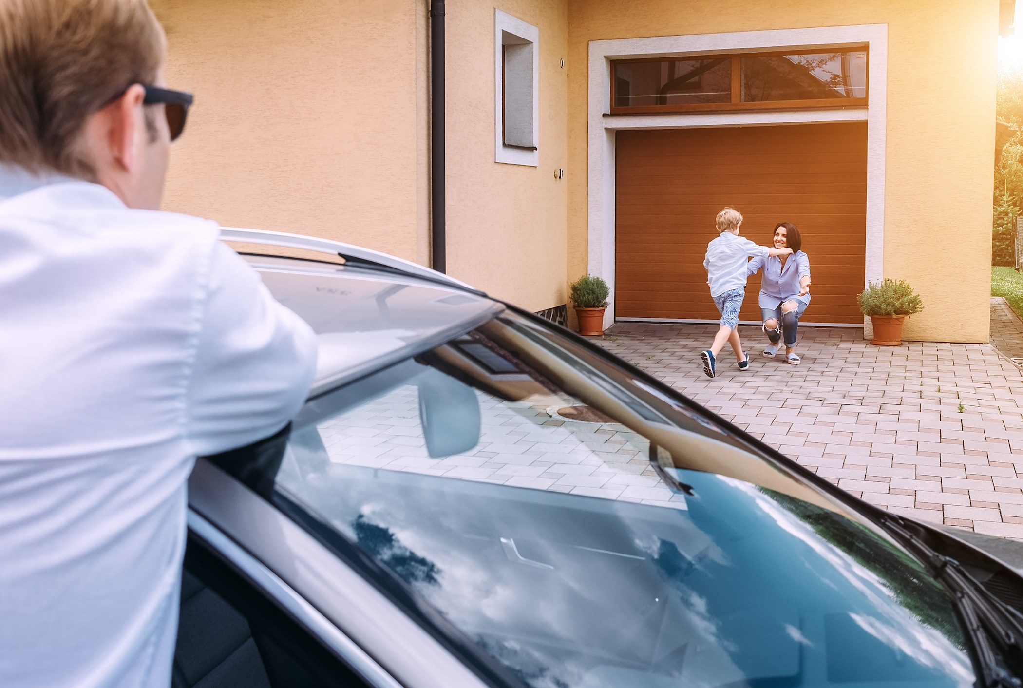 A son runs to his mother while father waits at the car.