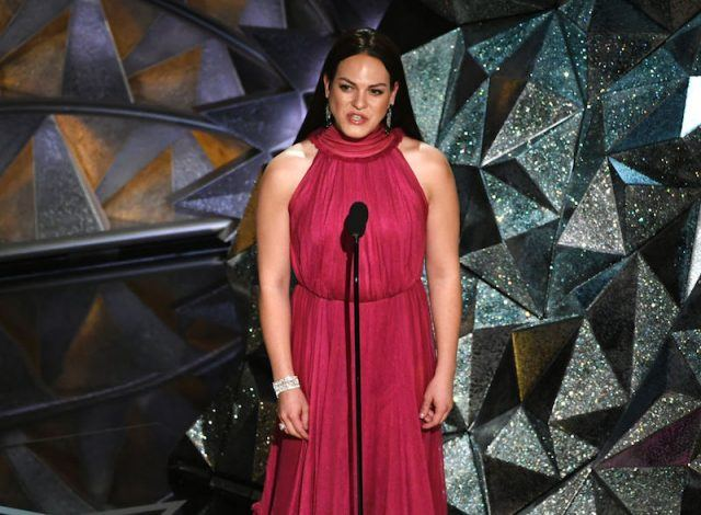Daniela Vega speaking in front of a microphone on stage.