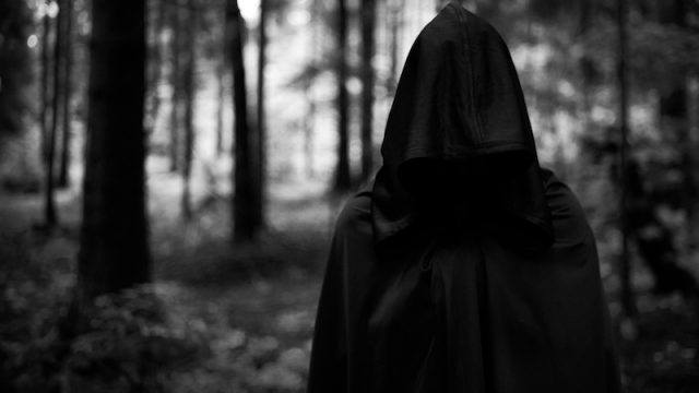 A dark hooded figure in a forest.