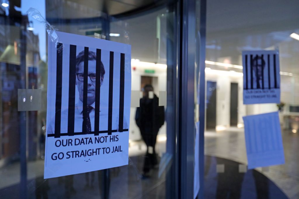 Posters depicting Cambridge Analytica's CEO Alexander Nix behind bars,