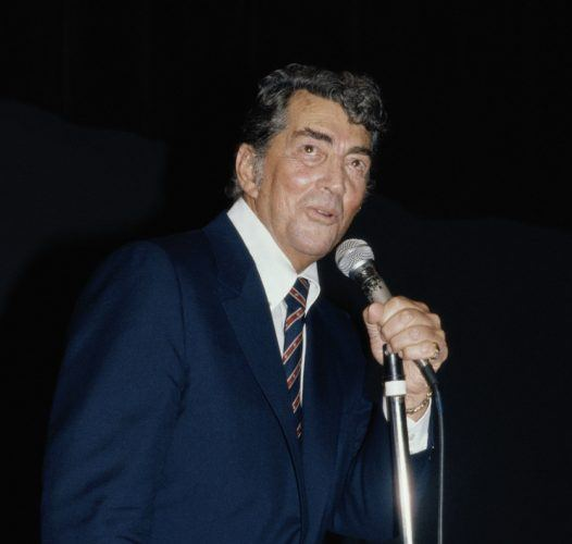 Dean Martin (1917-1995), US singer and actor, singing into a microphone at the Variety Club luncheon