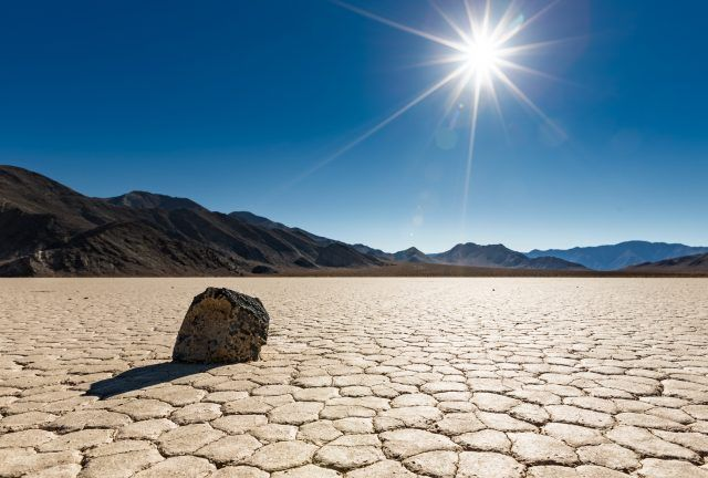 "A lone ""sailing rock"" sits basking in the bright unrelenting sun at Racetrack Playa in Death Valley National Park, California"