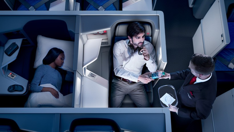 One passenger sleeping and one being given a water bottle on Delta one first class flight