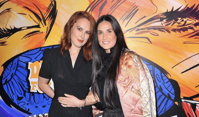 Rumor Willis and Demi Moore posing in front of a colorful background at a premiere.