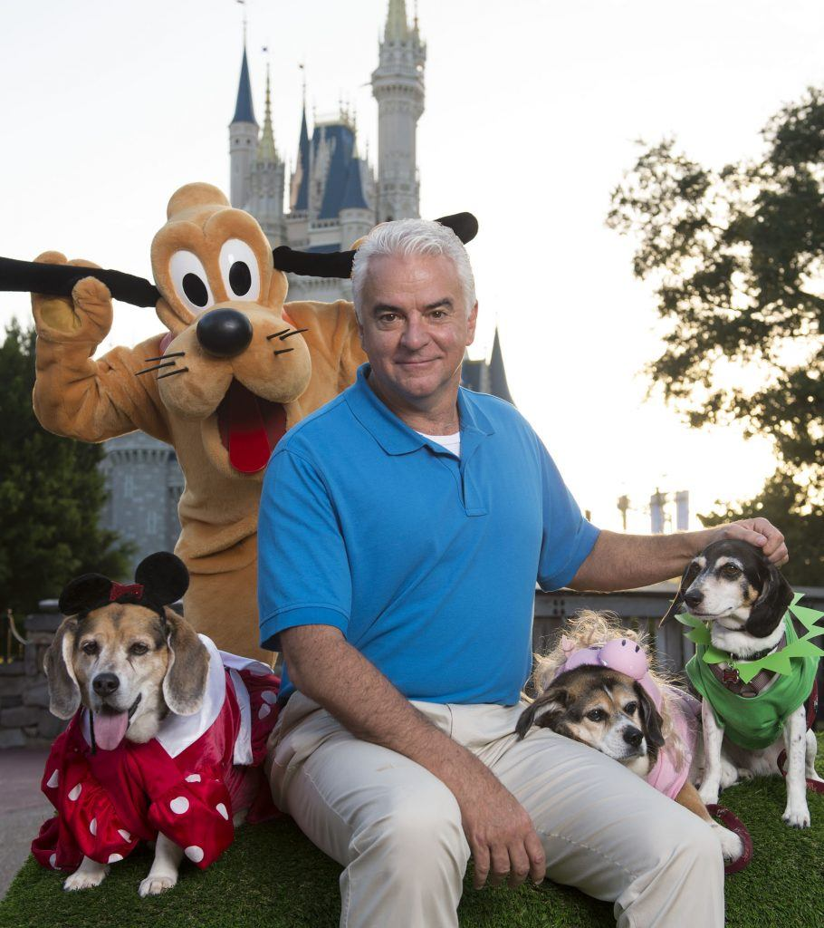 actor John O'Hurley poses with Pluto and three Disney-dressed dogs at the Magic Kingdom at Walt Disney World Resort