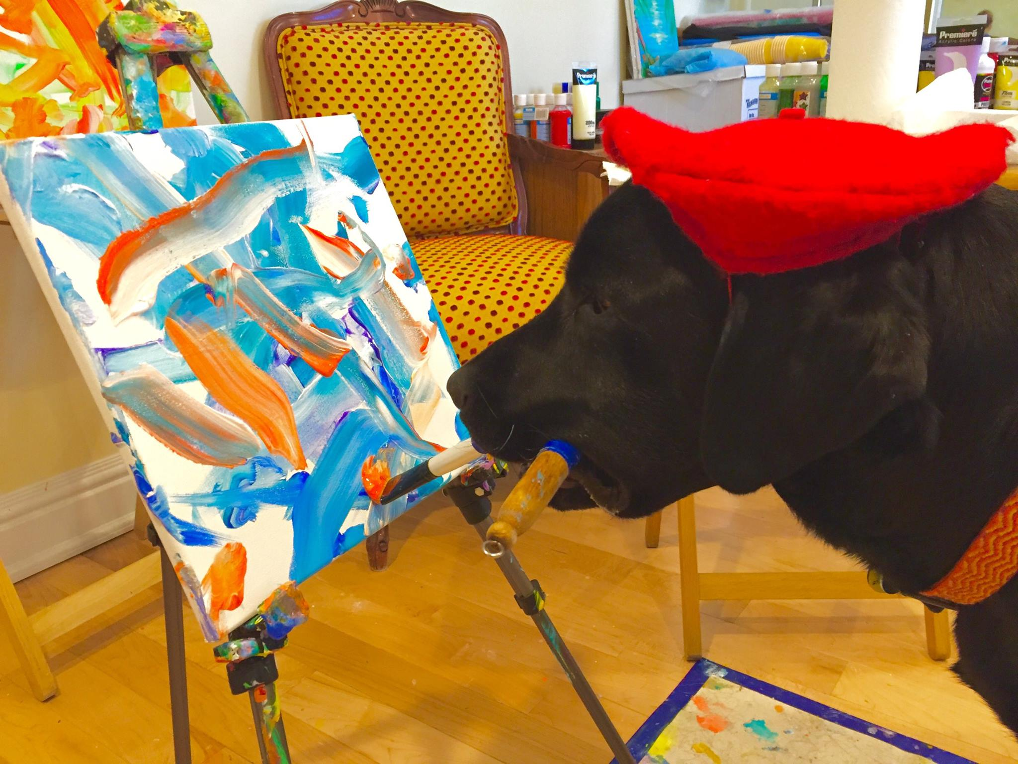 Dog wearing a red beret and painting