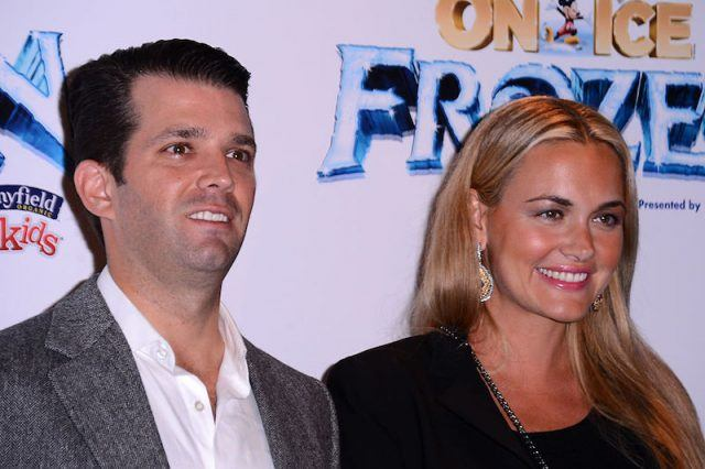 Donald Trump Jr. smiling on a red carpet with his wife.