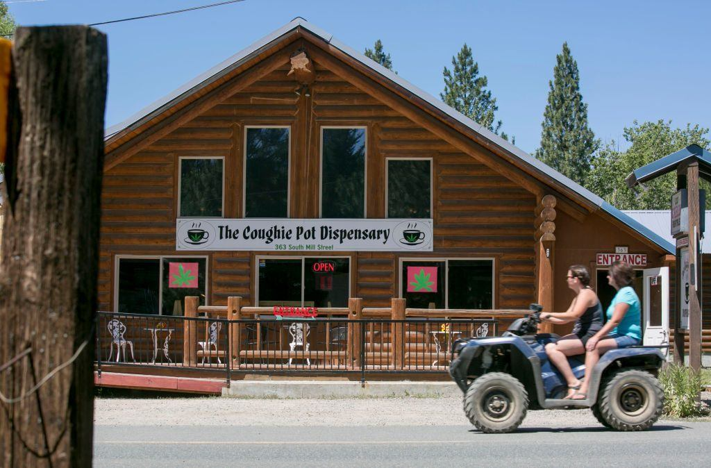 Tourists on a four-wheel leisure vehicle pass the Coughie Pot marijuana dispensary