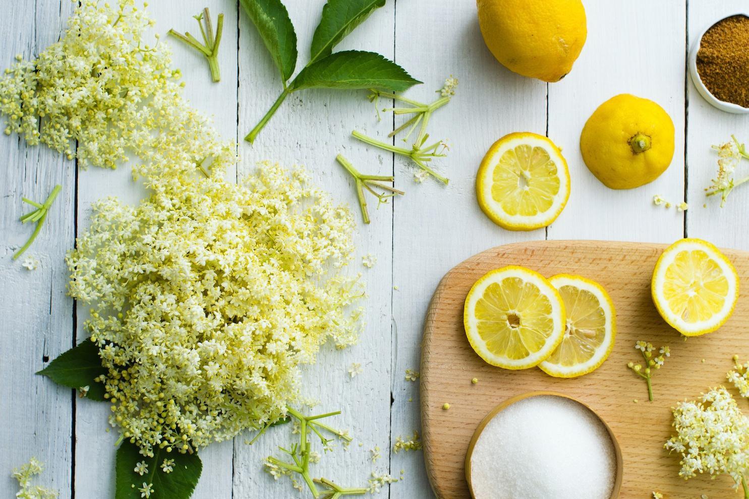 Elderflower and lemons on a white wood background