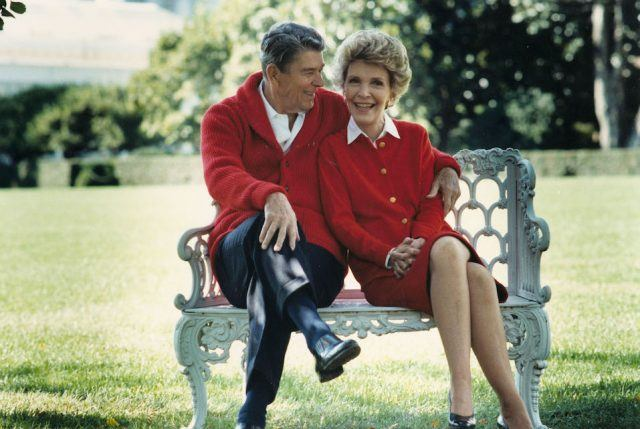 U.S. President Ronald Reagan and First Lady Nancy Reagan sit on a bench in matching red sweaters.