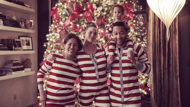 The family wears white and red matching pajamas in front of their Christmas tree.