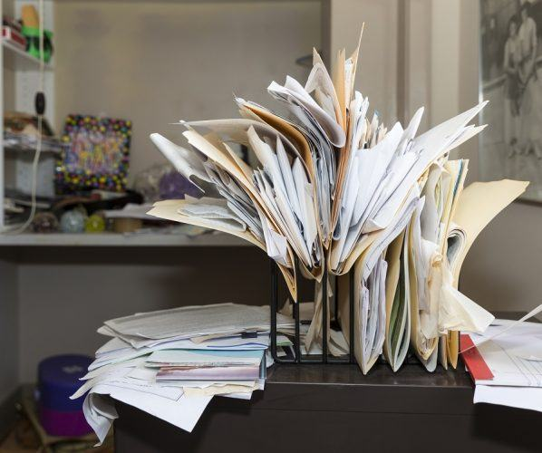 Messy, chaotic file rack on a desk in cluttered room