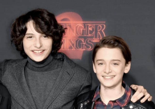 Finn and Noah posing together on a red carpet.