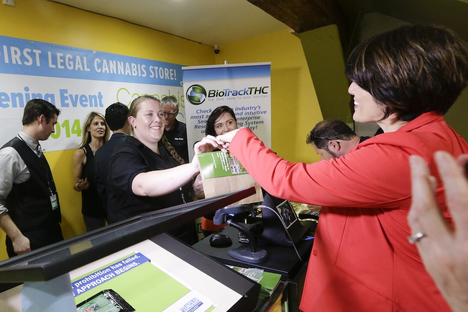 Alison Holcomb criminal justice director at the Washington state ACLU, buys marijuana at the Cannabis City retail marijuana store