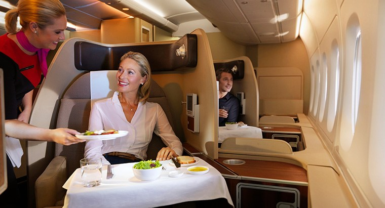 Woman being served food in Qantas airlines first class.