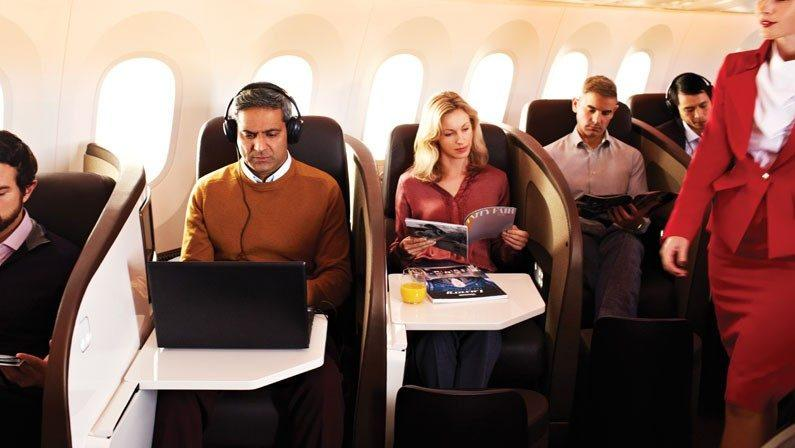 Passengers sitting and working in the first class section of Virgin Atlantic plane.
