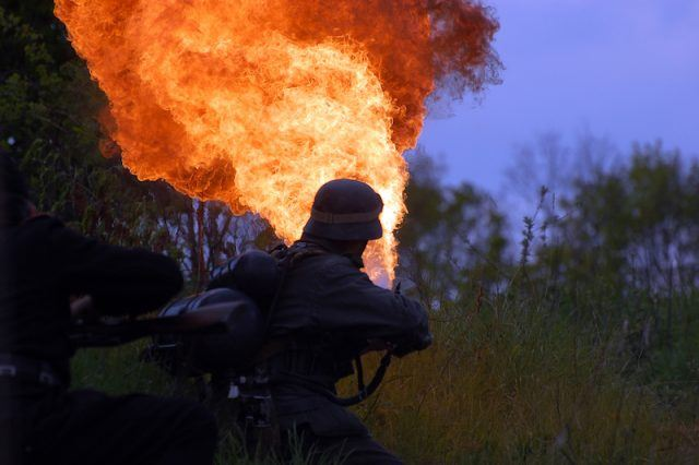 A person aiming a flame thrower.