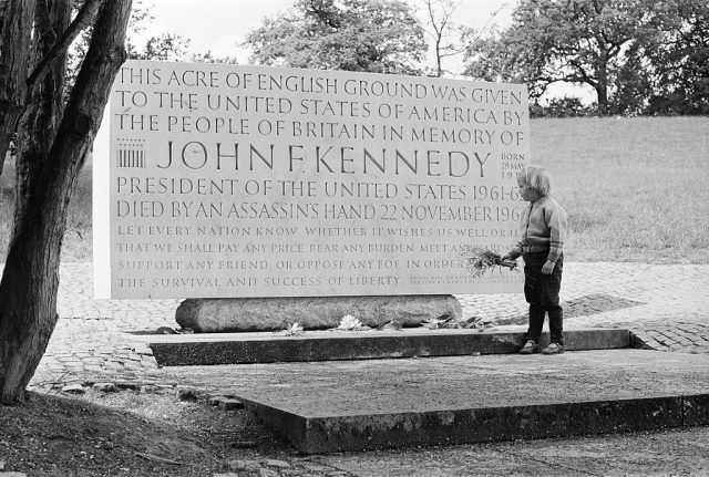 A young girl lays flowers at the John F Kennedy Memorial