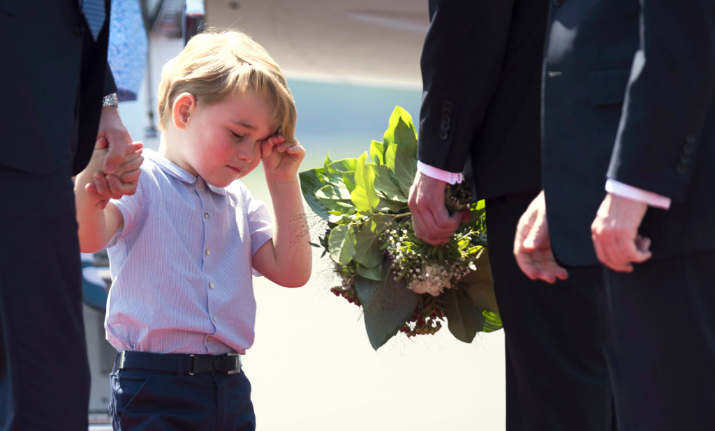 Prince George holds the hand of his father Britain's Prince William Duke of Cambridge, upon their arrival at the airport in Berlin