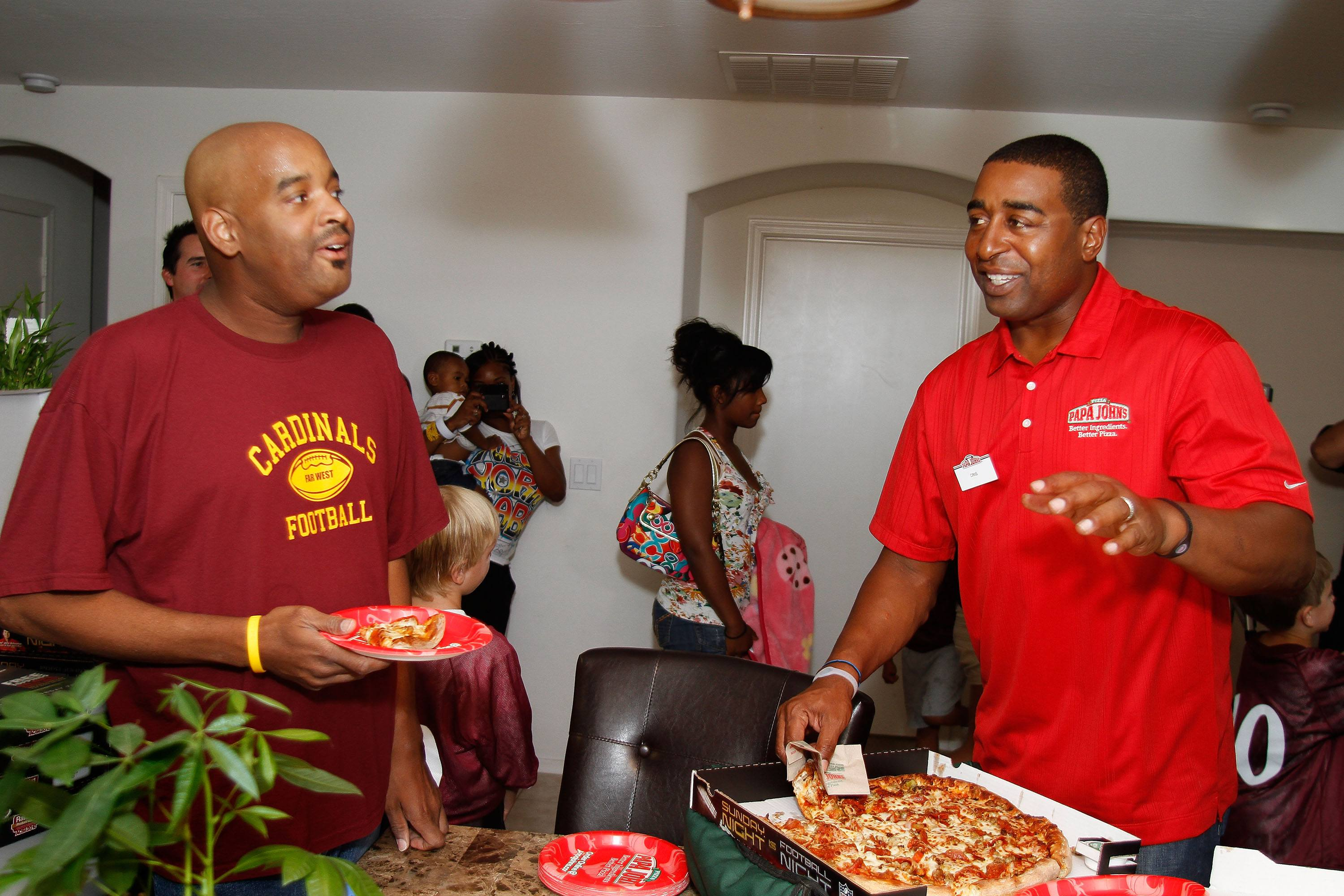 Papa Johns contest winner Anthony Green and Former NFL Star Cris Carter watch the NFL kickoff game on September 9, 2010 in Phoenix, Arizona.