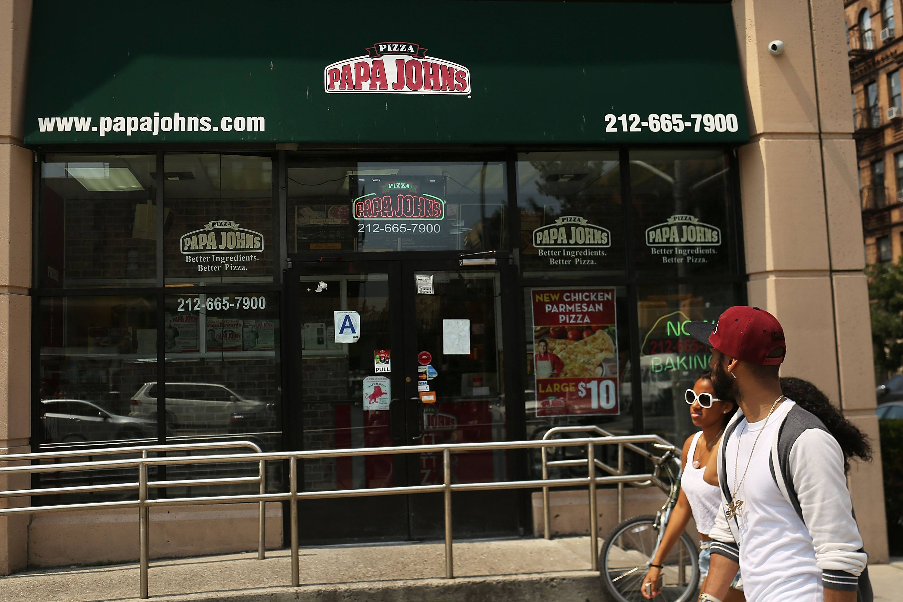 People walk by a Papa Johns pizza restaurant on August 9, 2012 in New York City.