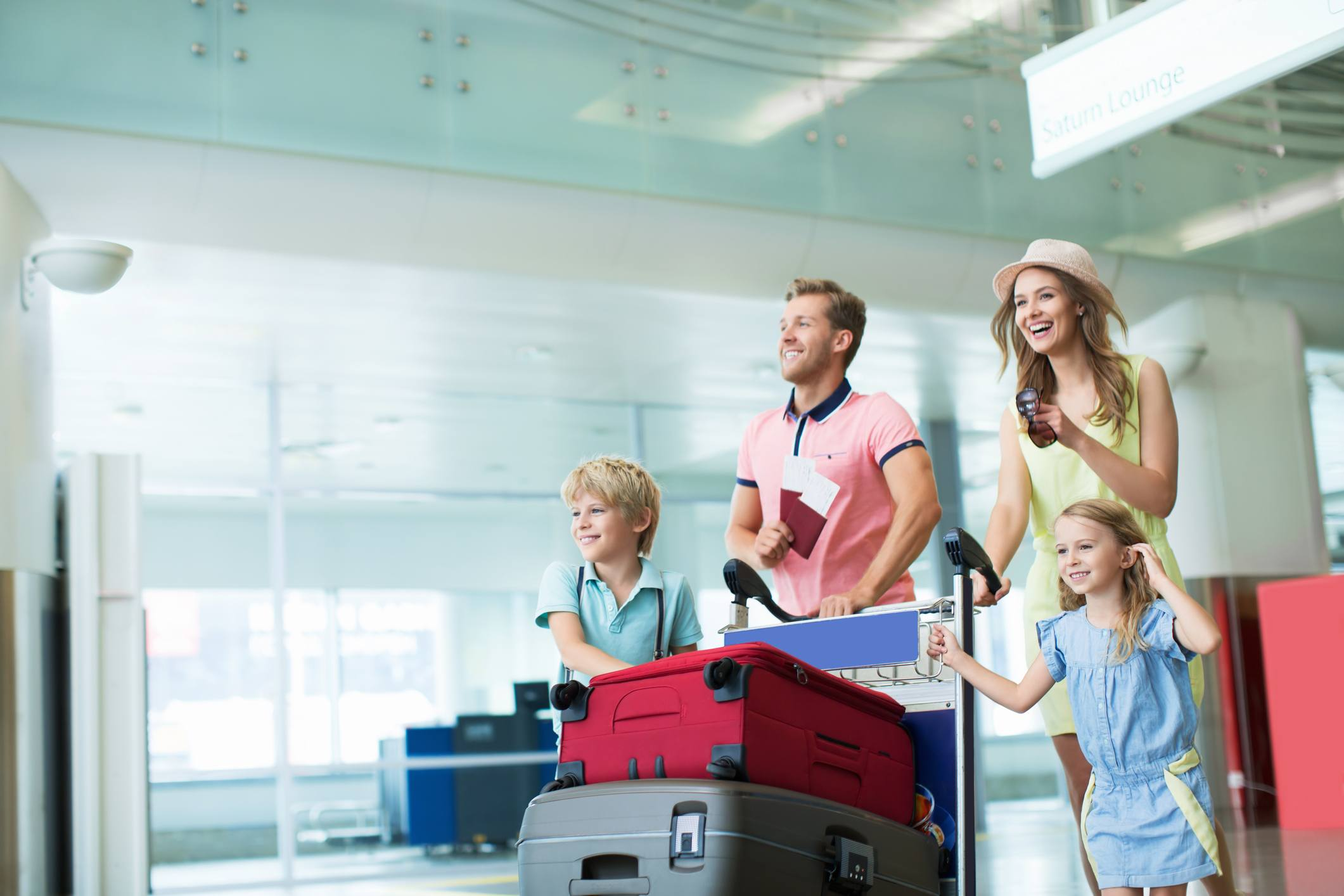family pushing luggage at the airport
