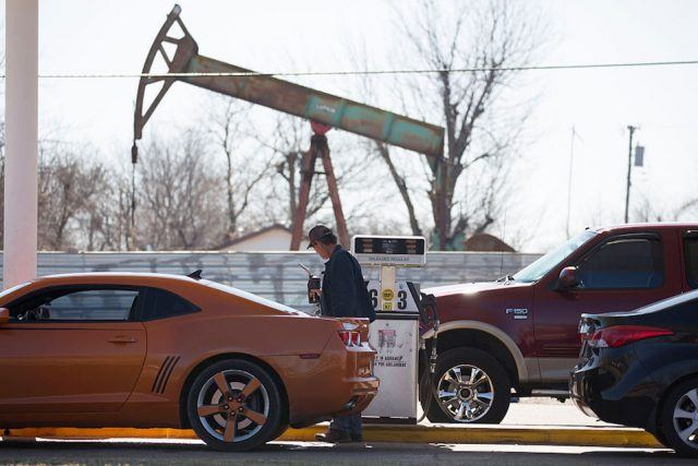 A motorist fills his car with gas at a gas station near an oil field pumping rig