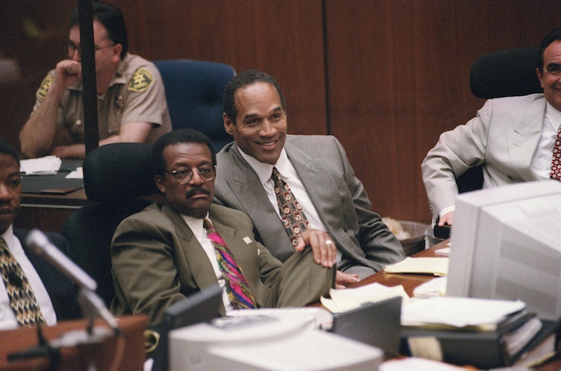"""LOS ANGELES, CA - MARCH 22: Murder defendant O.J. Simpson (C-R), seated next to his lawyer Johnnie Cochran, Jr. (C-L), smiles as witness Brian """"Kato"""" Kaelin testifies about acting job offers he has gotten as a result of publicity surrounding the night of the murders, during the O.J. Simpson double-murder criminal trial on March 22, 1995 in Los Angeles, California. The murder case is being televised internationally, due to global interest in the case where former American Football star and film actor O.J. Simpson has been charged with the stabbing murder of his former wife, Nicole Brown Simpson, and her friend Ronald Goldman. (Photo credit should read VINCE BUCCI/AFP/Getty Images) *** Local Caption *** O.J. Simpson;Johnnie Cochran"""