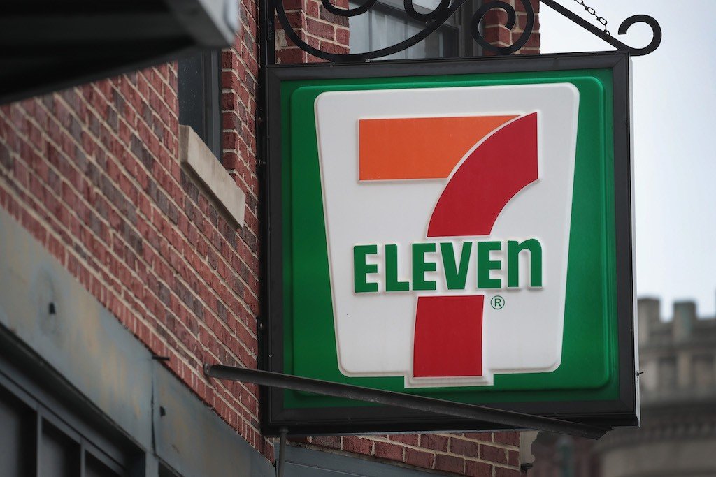 A sign hangs outside of a 7-Eleven store
