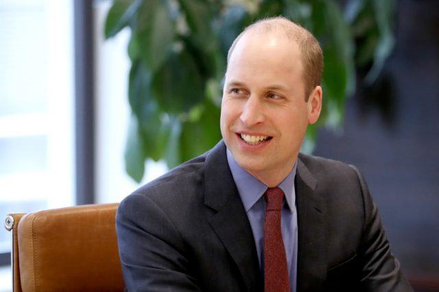 Prince William smiling while in a suit and tie.