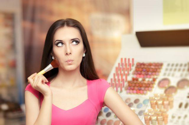 A woman applies makeup in front of a beauty counter.