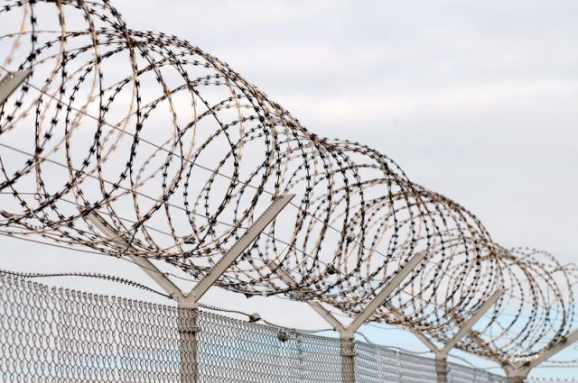 A jail gate seen with warped barbed wire.