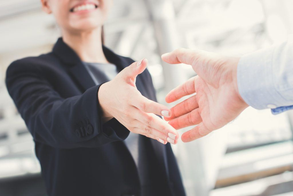two people in an office going in for a handshake