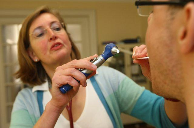 A family doctor checks a patient's mouth and throat at her office