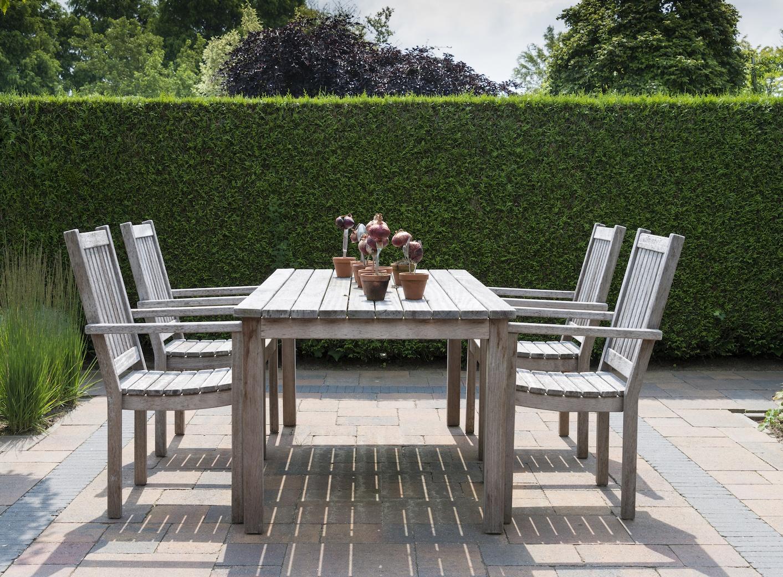 wooden garden furniture in garden with yew hedge