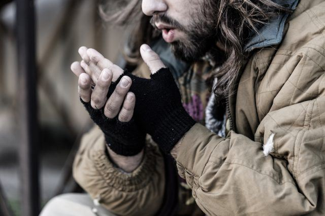 A man blows warm air into his cold hands.