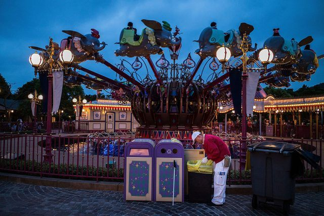 A staff member cleans the garbage bin inside Disneyland