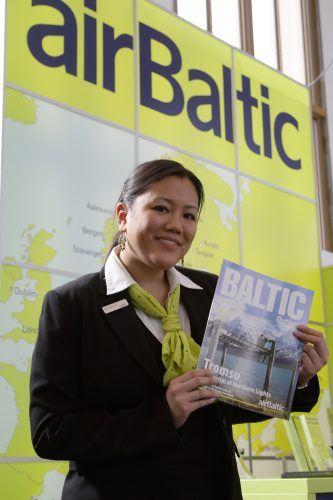 An employee of airliner Air Baltic holds a board magazin at the ITB